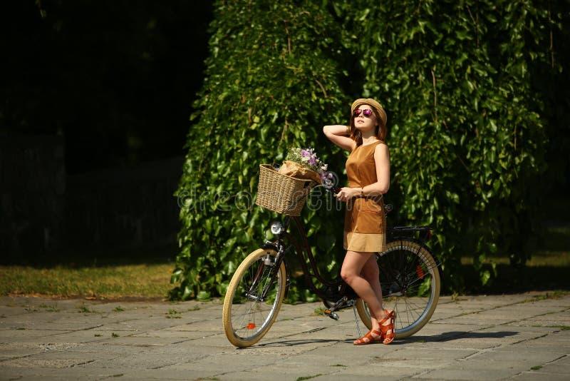 Mujer bastante joven con la bicicleta en el parque fotografía de archivo libre de regalías