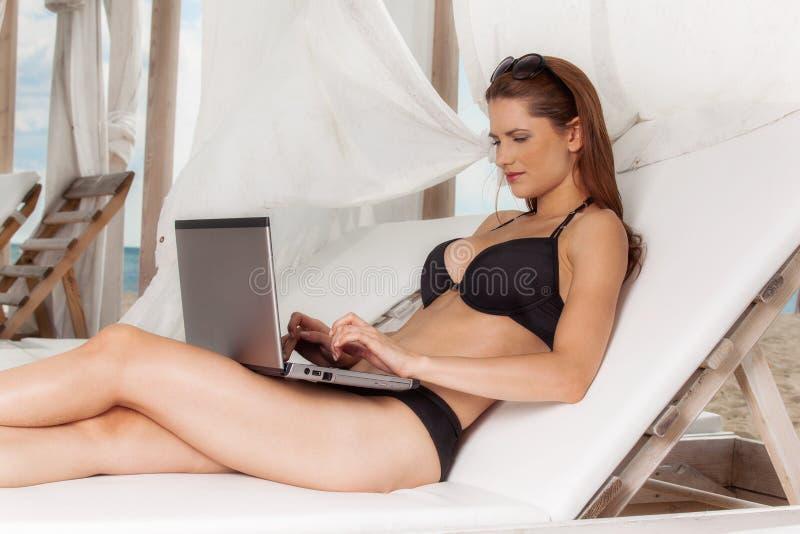 Mujer bastante joven con la computadora portátil fotografía de archivo libre de regalías
