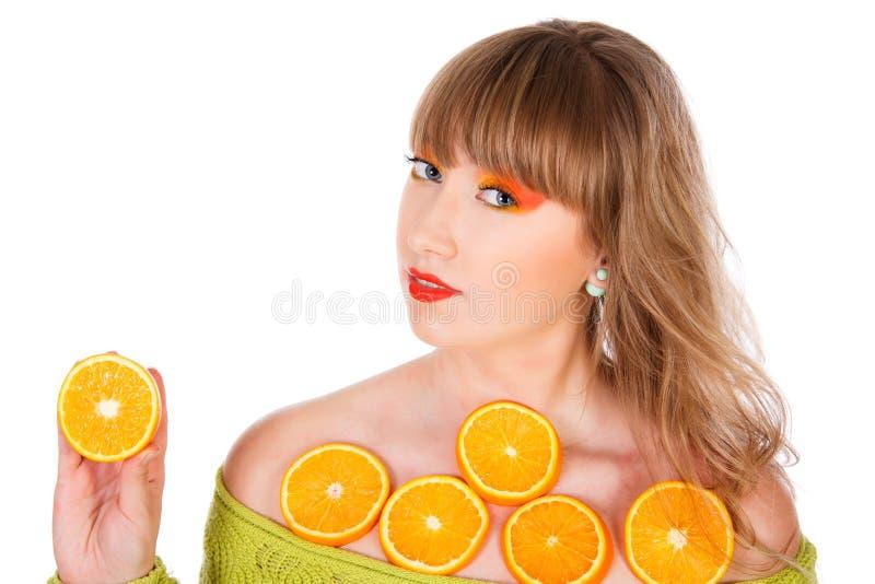Mujer bastante joven con las frutas anaranjadas cortadas foto de archivo libre de regalías