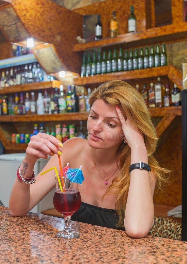 Mujer bastante joven con un cóctel que se sienta en fotos de archivo libres de regalías