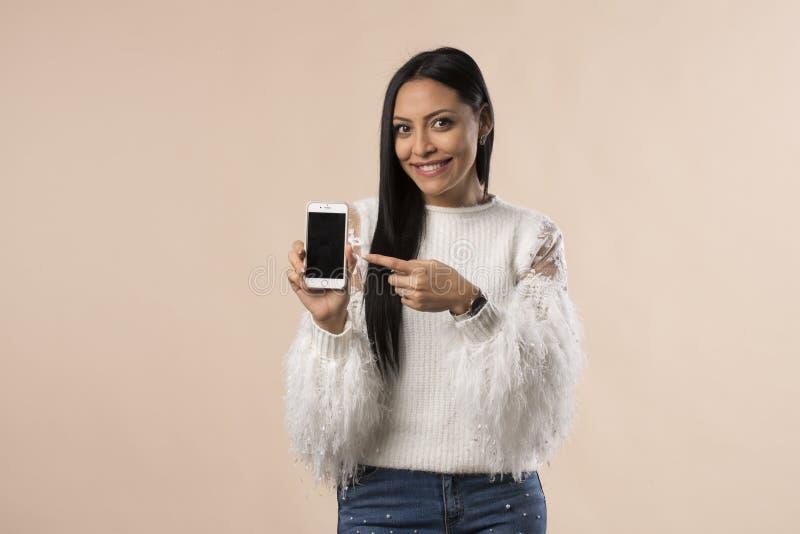 Mujer bastante joven de Latina que muestra la pantalla del teléfono foto de archivo libre de regalías