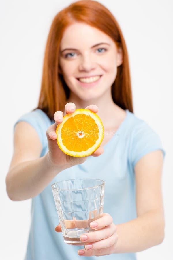 Mujer bastante joven del pelirrojo del positivo que muestra la mitad de la naranja fotografía de archivo
