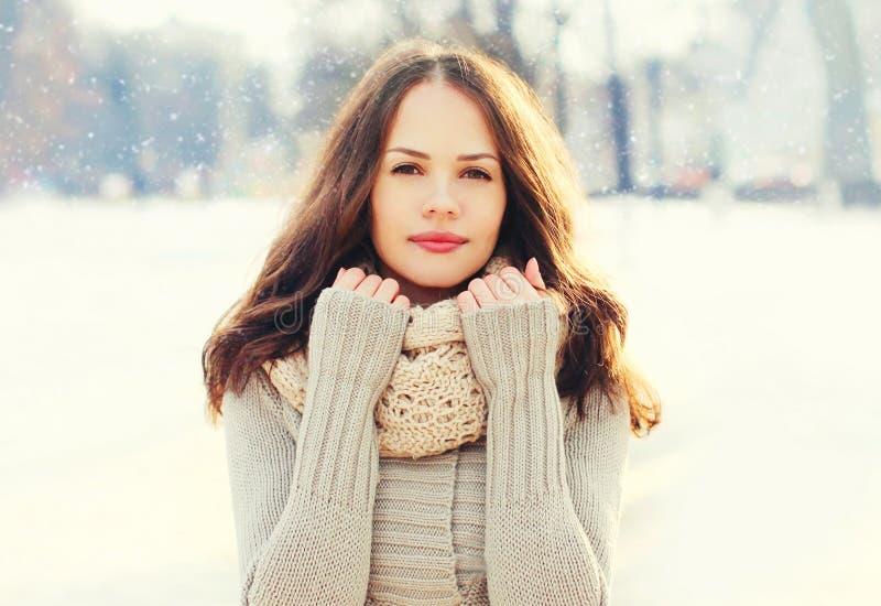 Mujer bastante joven del retrato que lleva un suéter y una bufanda hechos punto en invierno sobre los copos de nieve imagenes de archivo