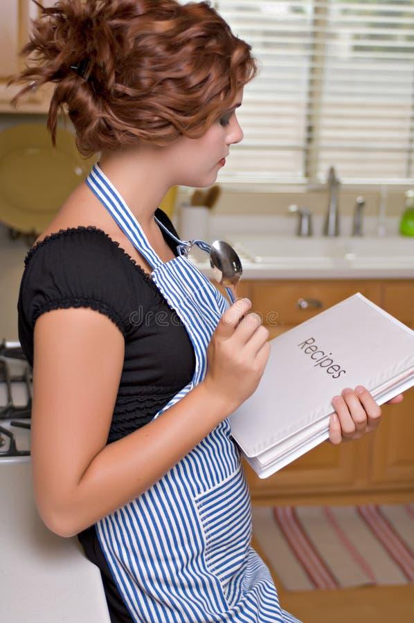 Mujer bastante joven en cocina imagenes de archivo