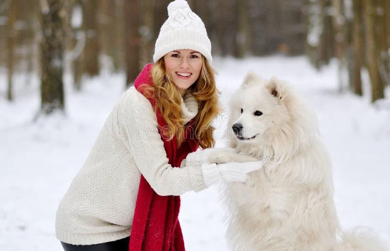Mujer bastante joven en el invierno Forest Walking con su samoyedo del blanco del perro fotografía de archivo libre de regalías