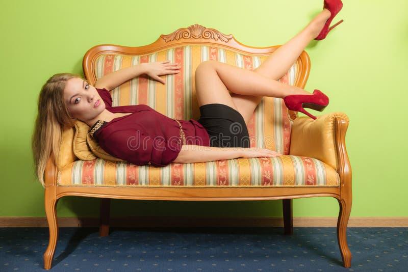 Mujer bastante joven en el sofá del vintage Moda imagen de archivo