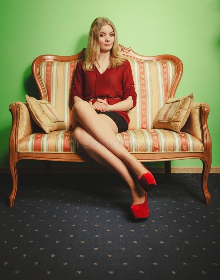 Mujer bastante joven en el sofá del vintage Moda imágenes de archivo libres de regalías