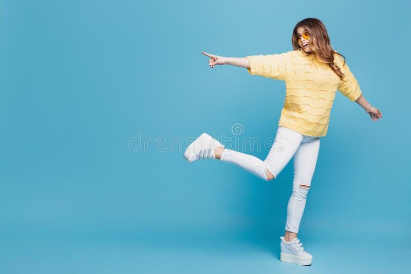 Mujer bastante joven en el suéter amarillo que presenta en fondo azul Mujer atractiva que señala los fingeres a la izquierda con fotografía de archivo libre de regalías