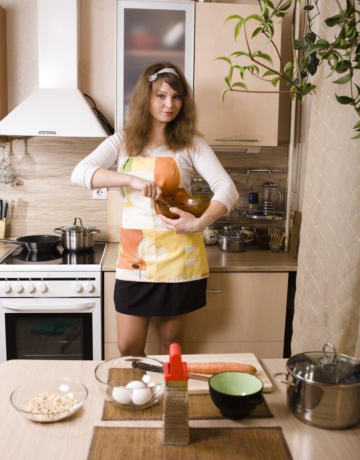 Mujer bastante joven en la cocina que prepara la cena fotografía de archivo