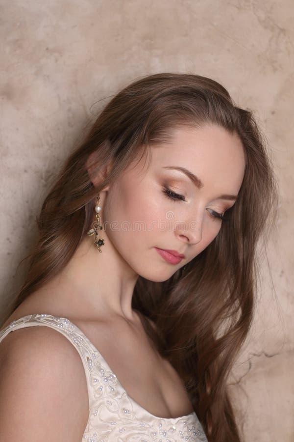 Mujer bastante joven en pendientes con el pelo largo imagen de archivo libre de regalías