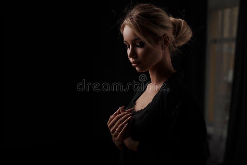 Mujer bastante joven en ropa negra en la noche en un cuarto oscuro fotografía de archivo libre de regalías
