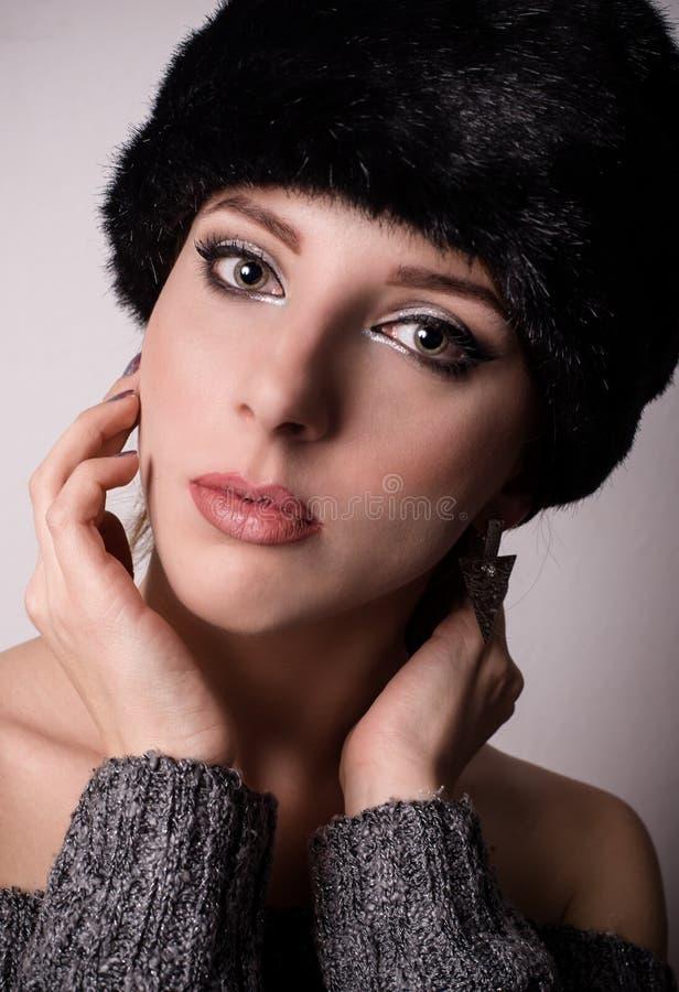 Mujer bastante joven en un sombrero de piel del invierno imagen de archivo