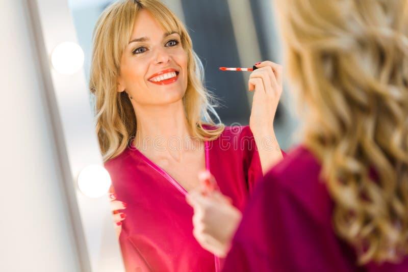 Mujer bastante joven que aplica maquillaje de los labios con el cepillo cosmético en salón de belleza fotografía de archivo