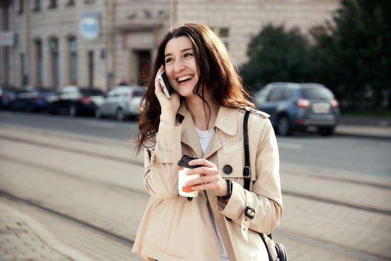 Mujer bastante joven que bebe la taza de café para llevar al aire libre, hablando en el teléfono, imagenes de archivo