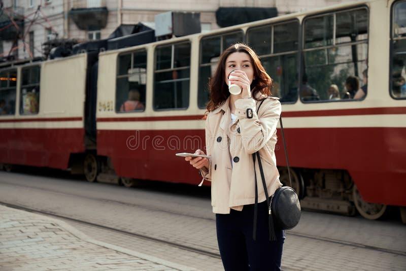 Mujer bastante joven que bebe la taza de café para llevar, usando el teléfono elegante mientras que espera el tren como llegada imagen de archivo