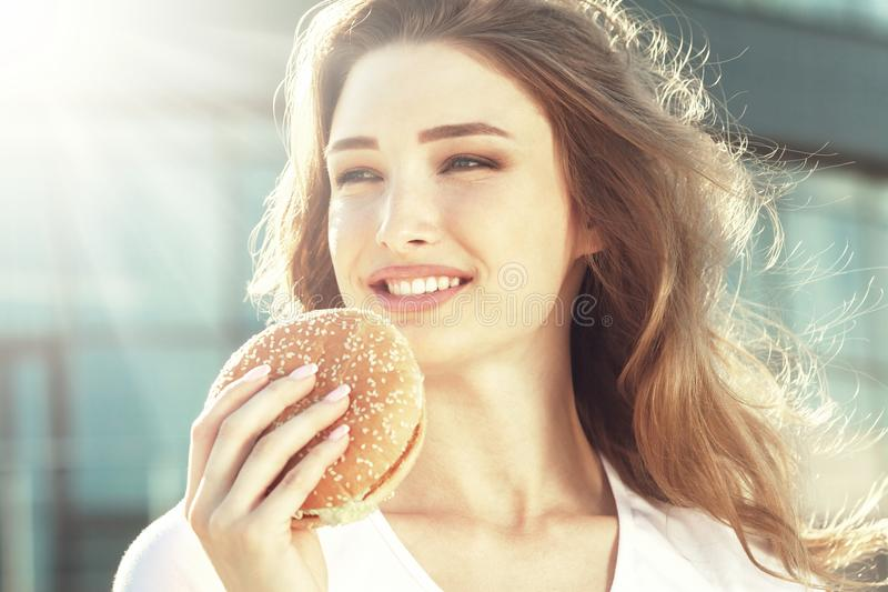 Mujer bastante joven que come la hamburguesa en la calle soleada de la ciudad foto de archivo libre de regalías