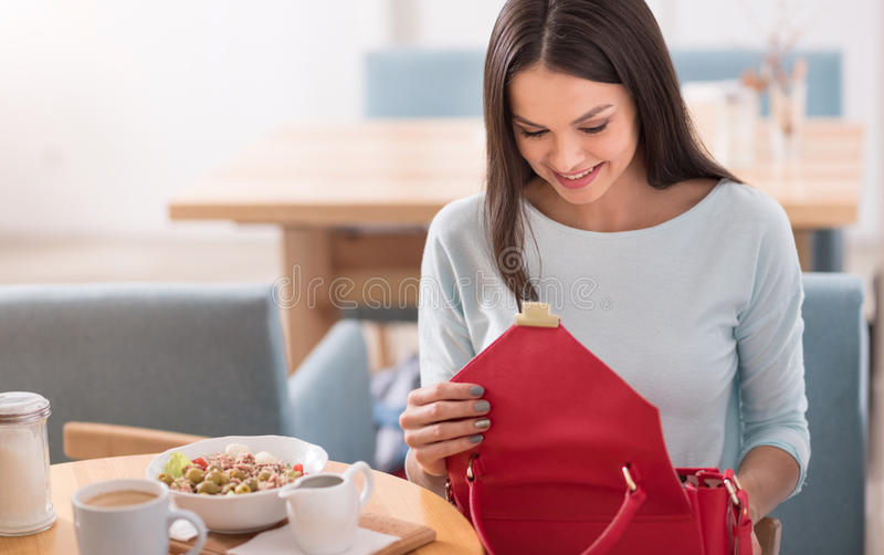 Mujer bastante joven que comprueba su bolso en un café fotografía de archivo