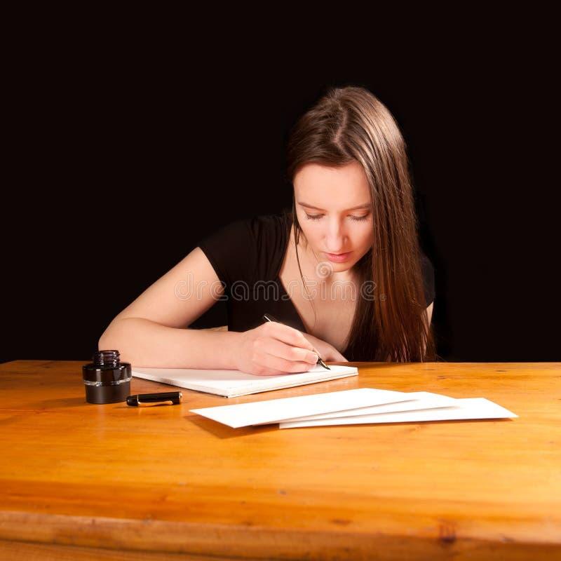Mujer bastante joven que escribe una letra fotos de archivo libres de regalías