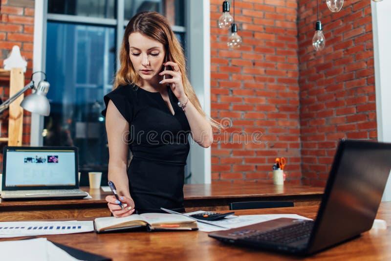 Mujer bastante joven que habla en el teléfono que cuenta usando una calculadora que trabaja en la oficina que se coloca en el esc imágenes de archivo libres de regalías