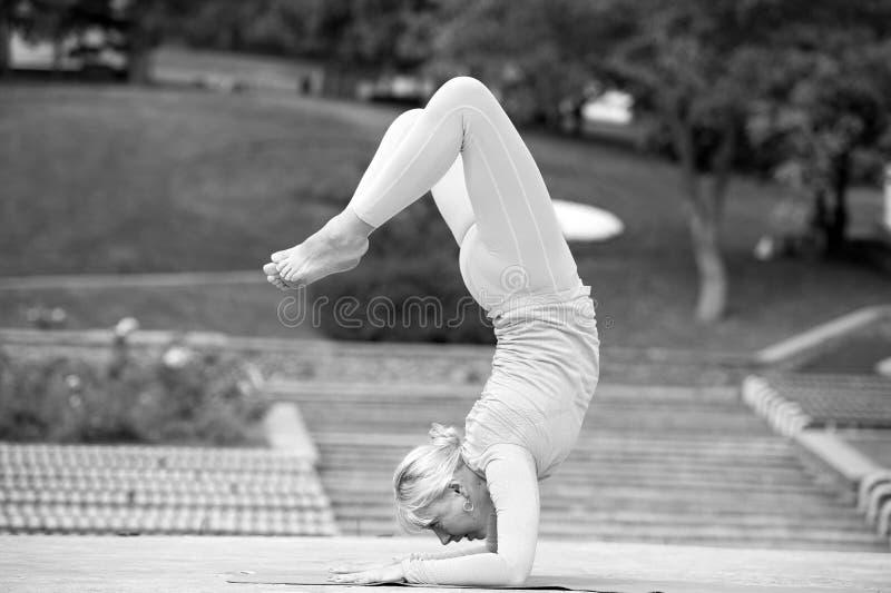 Mujer bastante joven que hace asanas de la yoga en el parque imágenes de archivo libres de regalías