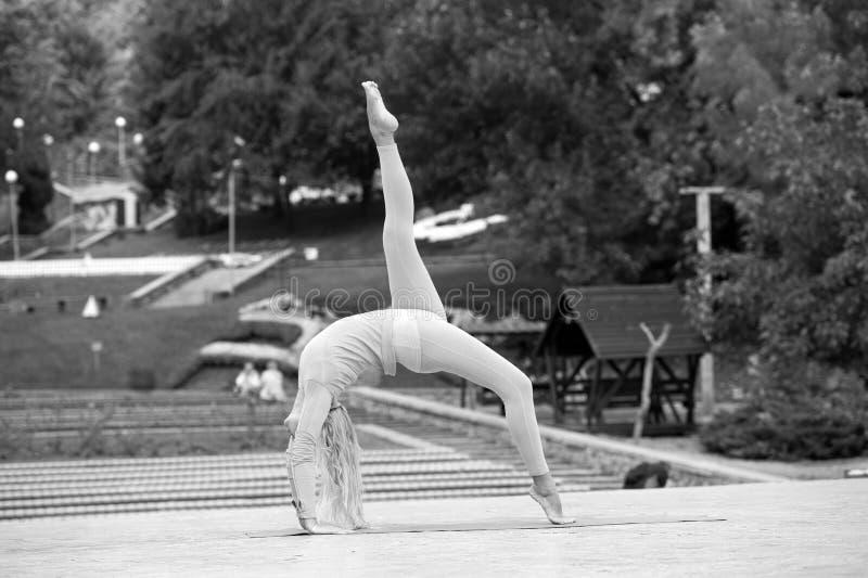 Mujer bastante joven que hace asanas de la yoga en el parque fotografía de archivo libre de regalías