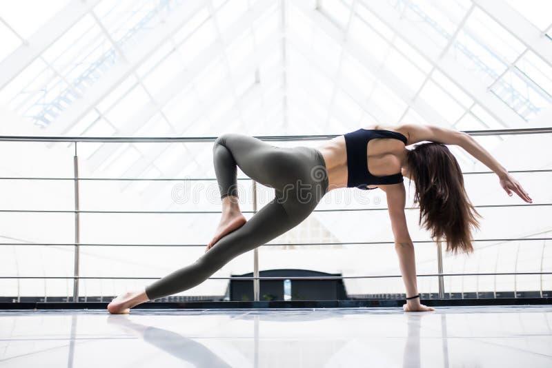 Mujer bastante joven que hace ejercicio de la YOGA en pasillo grande de la aptitud imagenes de archivo