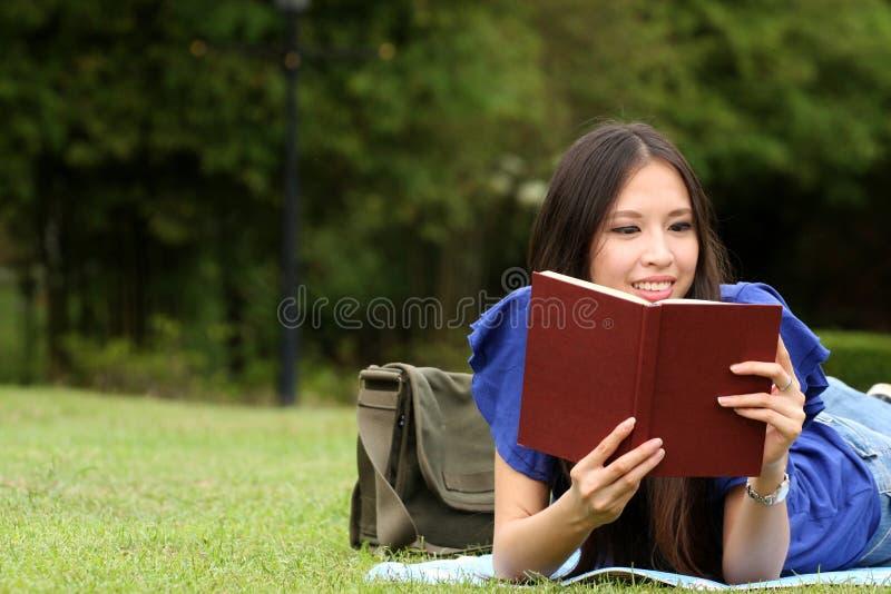 Mujer bastante joven que lee un libro en el parque fotografía de archivo libre de regalías
