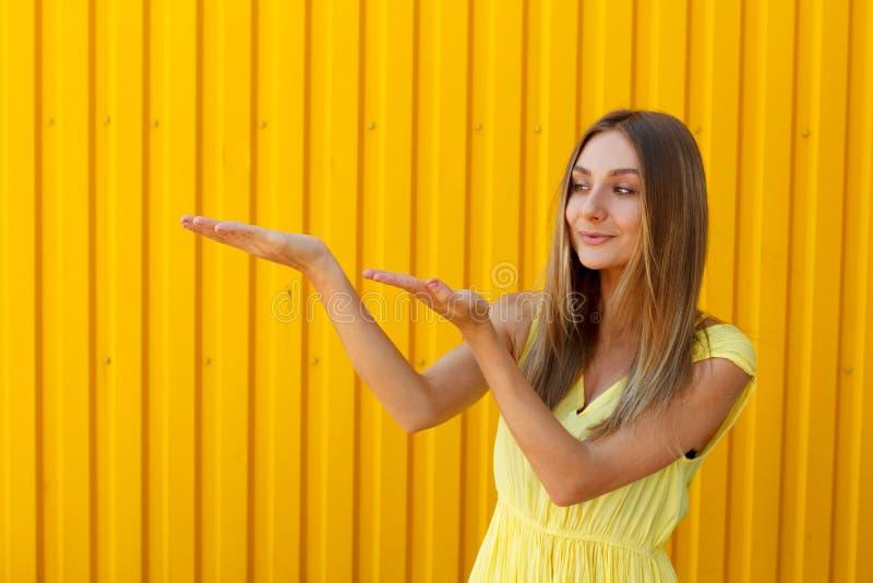Mujer bastante joven que lleva a cabo las manos sobre la presentación de su producto w imagen de archivo libre de regalías