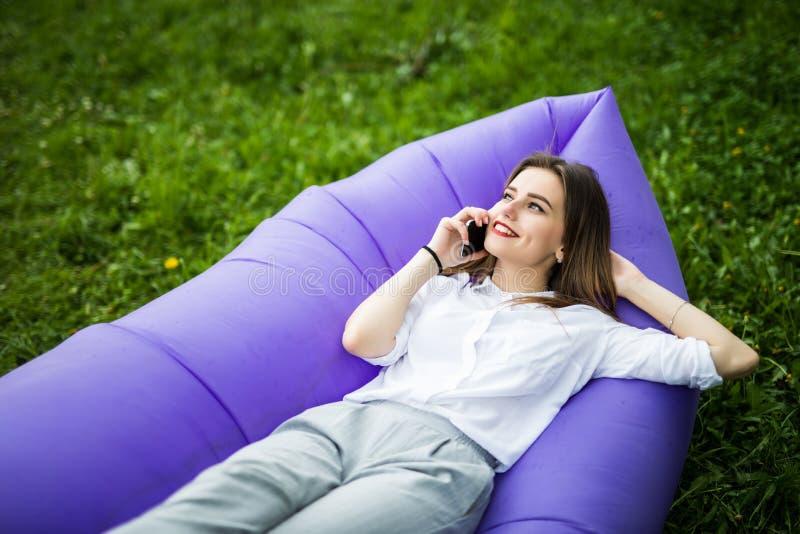 Mujer bastante joven que miente en charla inflable del lamzac del sofá sobre el teléfono mientras que descansa sobre hierba en pa fotos de archivo
