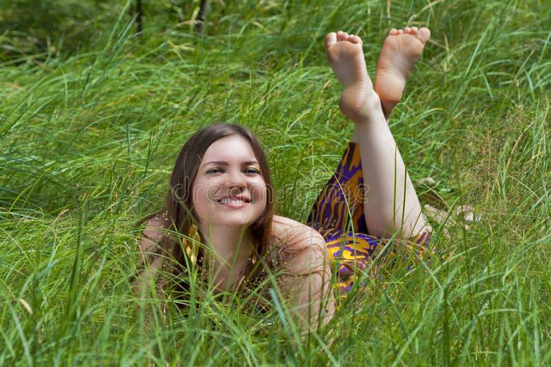Mujer bastante joven que miente en el césped del bosque imagenes de archivo