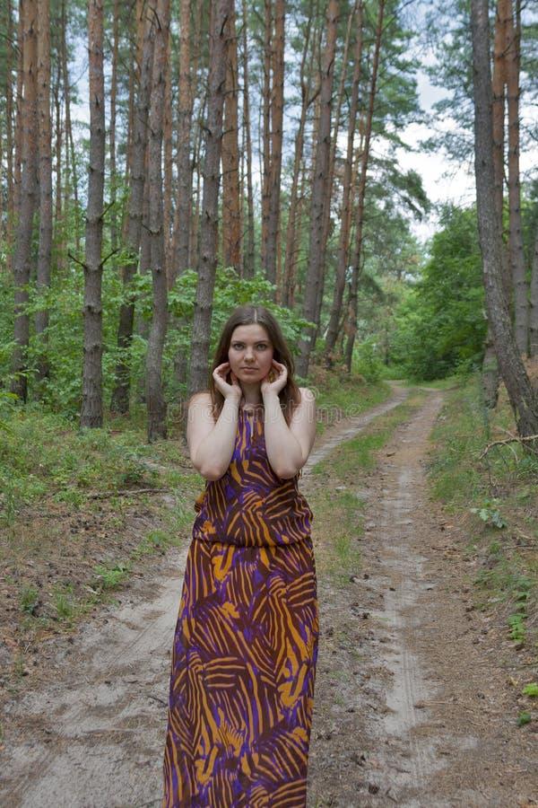 Mujer bastante joven que se coloca en el camino forestal imagen de archivo