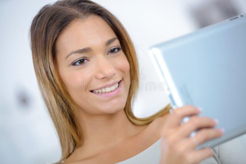 Mujer bastante joven que se relaja con la tableta foto de archivo