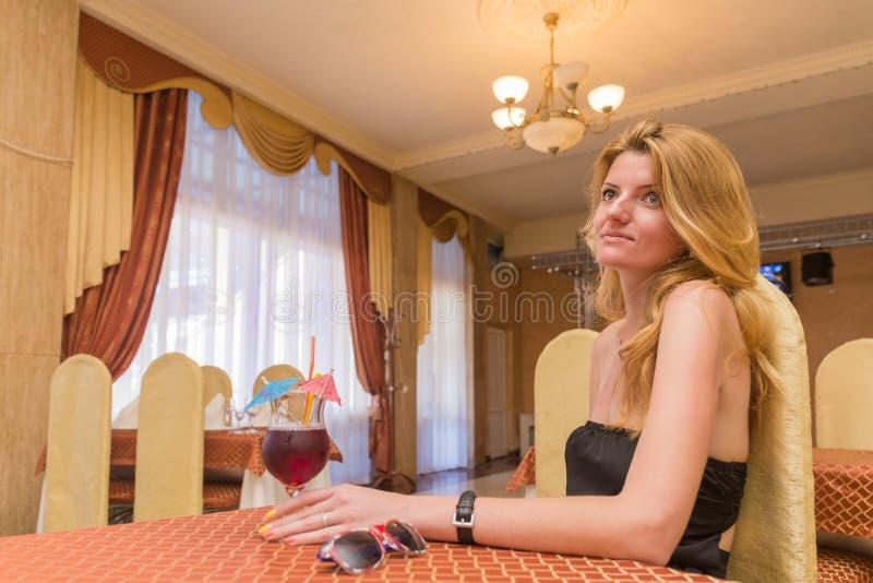 Mujer bastante joven que se sienta en el restaurante foto de archivo