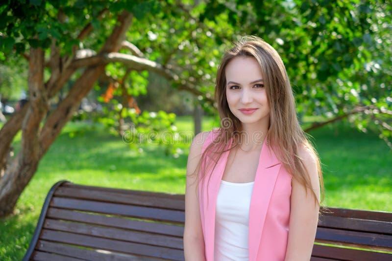 Mujer bastante joven que se sienta en un banco en el parque fotografía de archivo