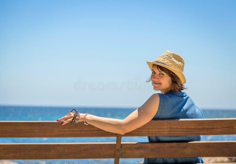 Mujer bastante joven que se sienta solamente en un banco delante del mar fotos de archivo libres de regalías