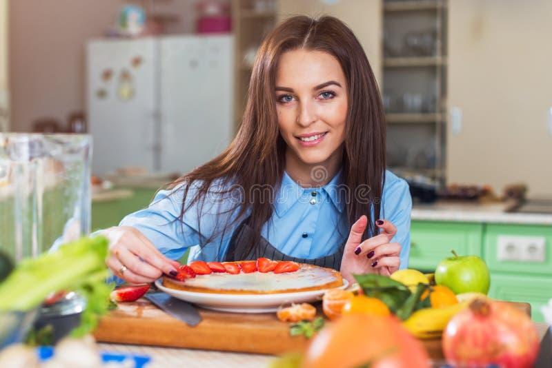 Mujer bastante joven que sonríe en la cámara mientras que adorna una torta con la fresa cortada que se sienta en cocina grande imagen de archivo libre de regalías
