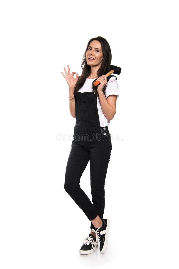 Mujer bastante joven que sostiene el martillo y que muestra la muestra aceptable imagen de archivo