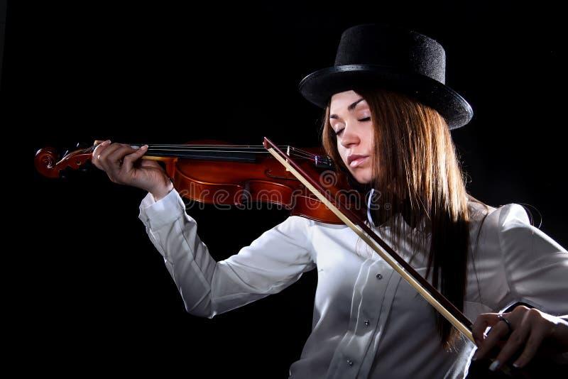 Mujer bastante joven que toca un violín fotografía de archivo