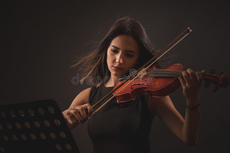 Mujer bastante joven que toca un violín sobre fondo negro foto de archivo libre de regalías