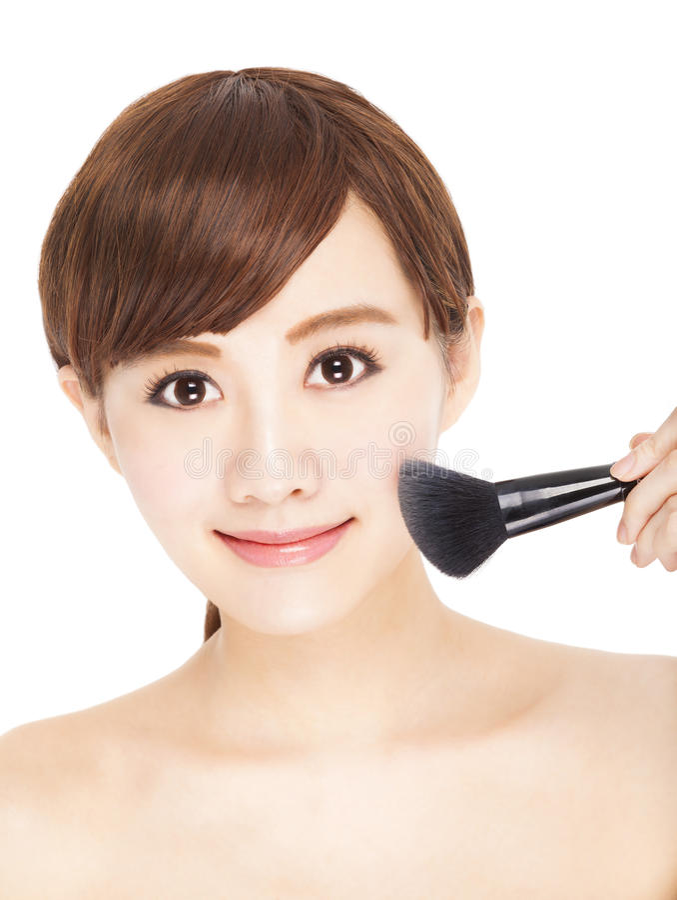 Mujer bastante joven que usa maquillaje de los cepillos su cara fotografía de archivo