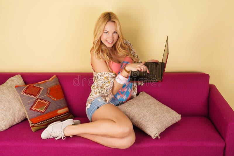 Mujer bastante joven que usa su ordenador portátil mientras que se relaja en un sofá foto de archivo libre de regalías
