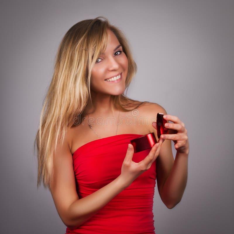 Mujer bastante joven rubia con la tarjeta del día de San Valentín presente en manos en re foto de archivo libre de regalías