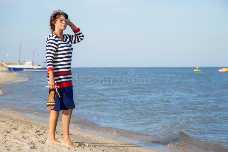 Mujer bastante mayor el vacaciones en la playa fotos de archivo