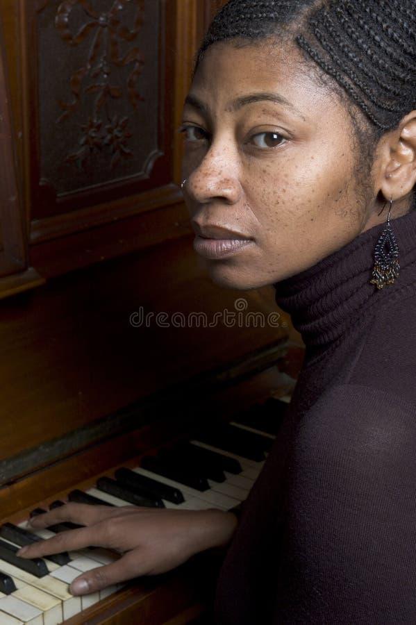 Mujer bastante negra en el piano fotos de archivo libres de regalías