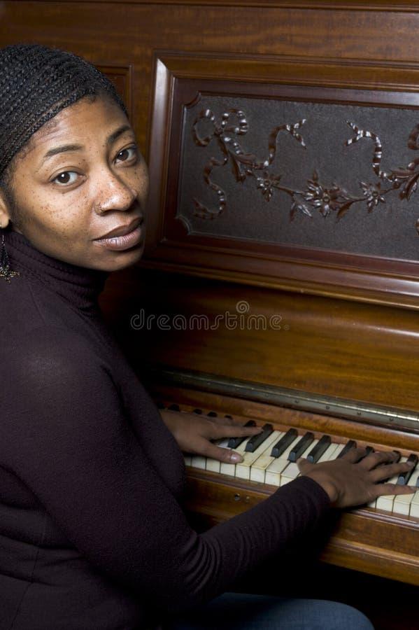 Mujer bastante negra en el piano fotos de archivo