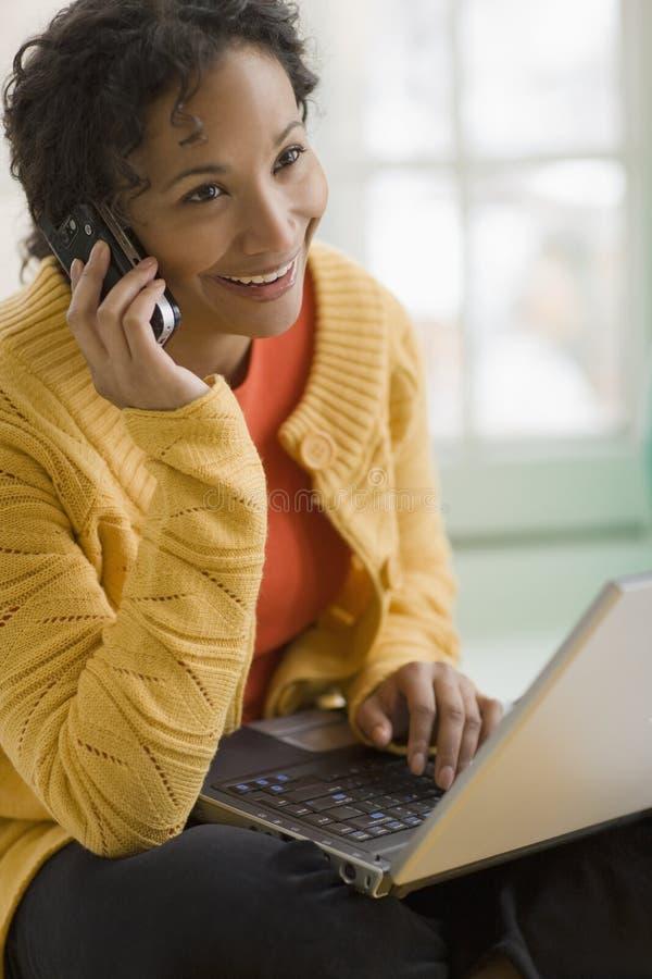 Mujer bastante negra en el teléfono celular y la computadora portátil foto de archivo libre de regalías
