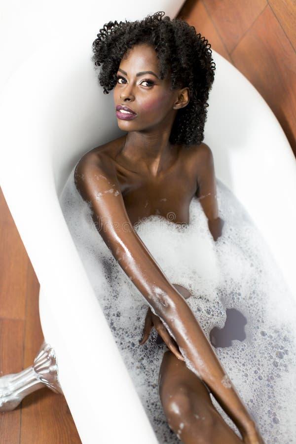Mujer bastante negra que tiene un baño fotos de archivo libres de regalías