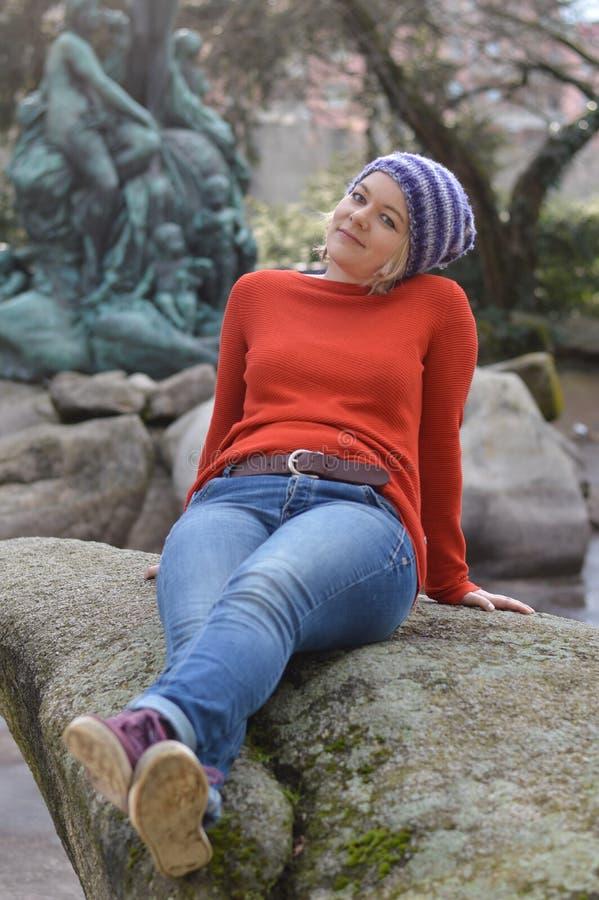 Mujer bastante rubia con el casquillo de punto que se sienta en un parque en una roca foto de archivo libre de regalías