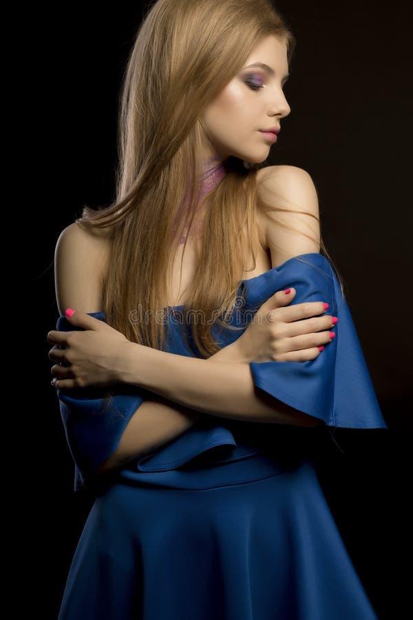 Mujer bastante rubia con el pelo enorme largo y el vestido azul con el nake fotografía de archivo libre de regalías