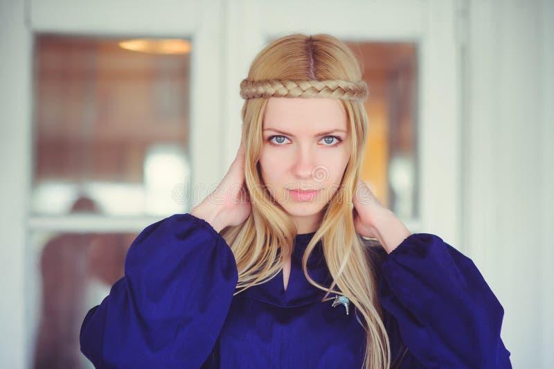 Mujer bastante rubia con el pelo trenzado, vestido en un vestido azul, retrato hermoso en la casa, imagen casera simple, cuidado  fotografía de archivo libre de regalías